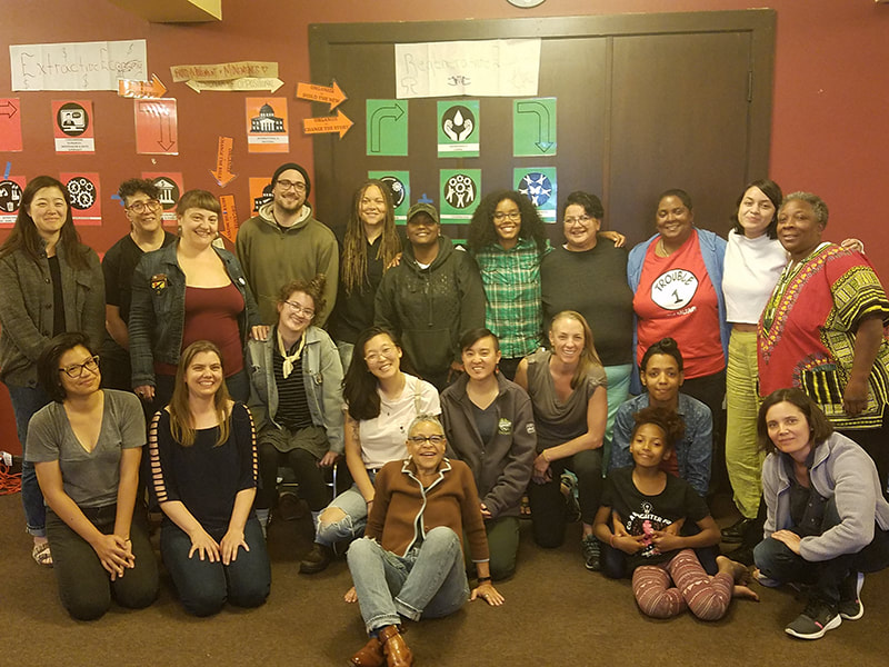 a group of 21 racially and age diverse people sit, kneel and stand in a room with red/brown walls. on the walls are posters demonstrating the path from extractive to regenerative economies.