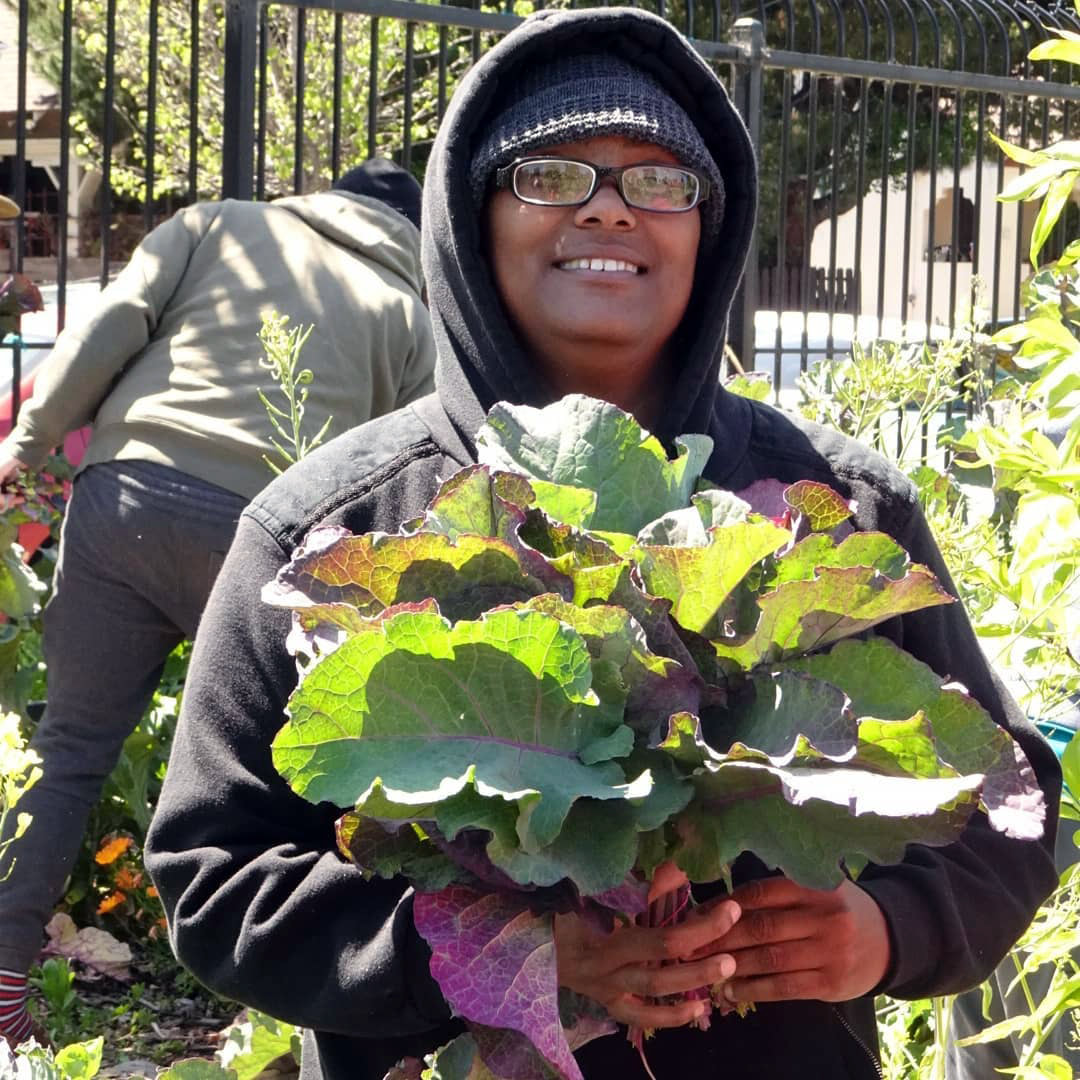 Photo of Karla from our permaculture workshop. She is smiling and holding a bunch of kale.