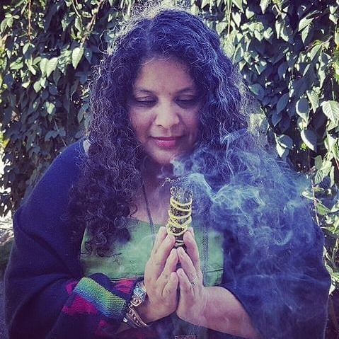 Photo of Brenda Salgado, who is looking down at the burning bundle of sage that she is holding in prayer hands.