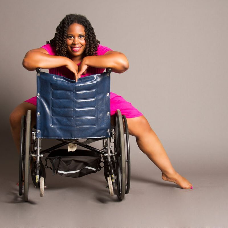 Photo of India Harville, who is smiling into the camera while striking a pose on her backwards-facing wheelchair.
